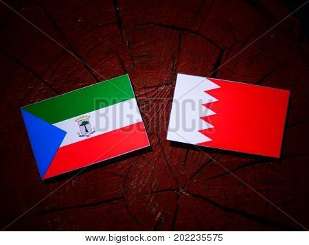 Equatorial Guinea Flag With Bahraini Flag On A Tree Stump Isolated