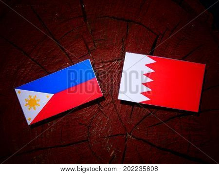 Philippines Flag With Bahraini Flag On A Tree Stump Isolated