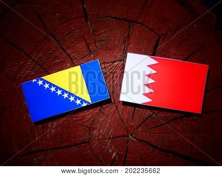 Bosnia And Herzegovina Flag With Bahraini Flag On A Tree Stump Isolated