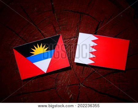 Antigua And Barbuda Flag With Bahraini Flag On A Tree Stump Isolated