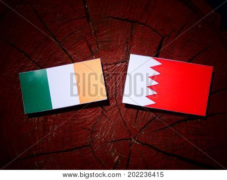 Irish Flag With Bahraini Flag On A Tree Stump Isolated