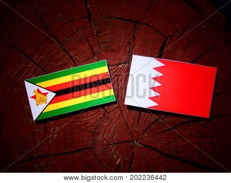 Zimbabwe Flag With Bahraini Flag On A Tree Stump Isolated