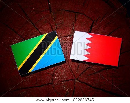 Tanzanian Flag With Bahraini Flag On A Tree Stump Isolated