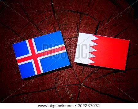 Icelandic Flag With Bahraini Flag On A Tree Stump Isolated