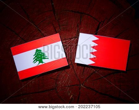 Lebanese Flag With Bahraini Flag On A Tree Stump Isolated
