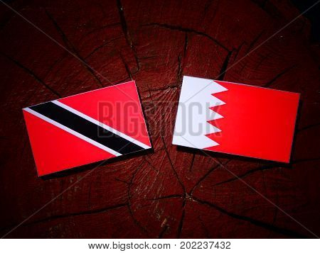 Trinidad And Tobago Flag With Bahraini Flag On A Tree Stump Isolated
