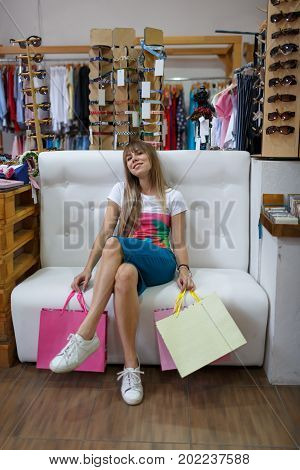 A portrait of a tired young woman on a shop background. A weak female holding her stylish purchases and sitting on a white sofa in a clothing store. Shopping, consumerism, money concept. Copy space.