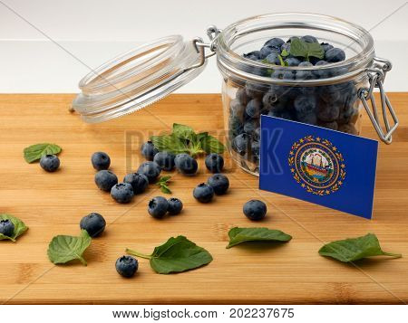 New Hampshire Flag On A Wooden Plank With Blueberries Isolated On White