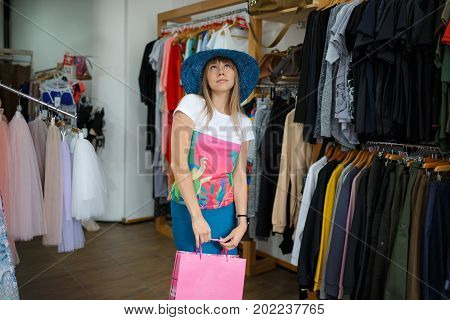 Shopping concept. A close-up portrait of a standing young woman on a clothing store background. A stylish female with a bright shopping bag trying on a beautiful hat in a clothing store. Copy space