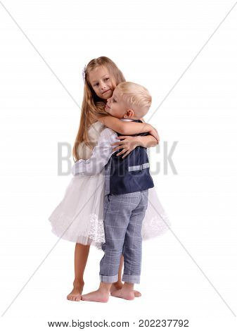 A pair of little siblings posing isolated over the white background. A pretty girl in a fancy dress and a boy in a classy suit hugging each other. Friendship and happy childhood concept.