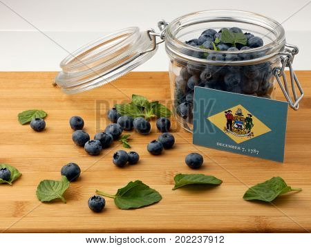 Delaware Flag On A Wooden Plank With Blueberries Isolated On White