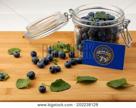 Nebraska Flag On A Wooden Plank With Blueberries Isolated On White