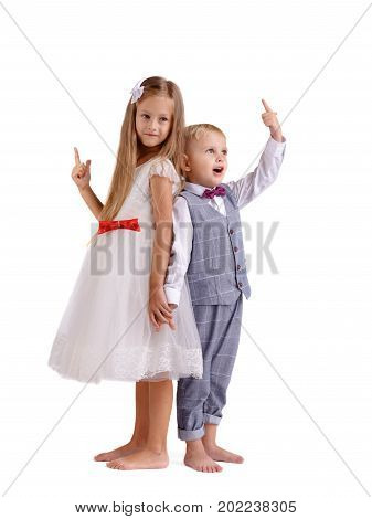 A pair of little siblings posing isolated over the white background. A charming girl in a fancy dress and a boy in a classy suit pointing at something. Friendship and happy childhood concept.