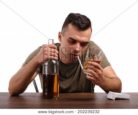 A sad, depressed man is holding a big bottle, glass full of whiskey and a cigarette, isolated on a white background. A boozed guy with an alcoholic drink and pack of cigarettes at a wooden table.