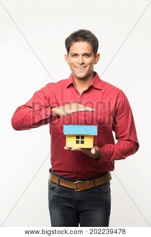 stock photo of Indian handsome young man holding conceptual house model made up of card board and standing over white background. Cheerful asian man with house model showing real estate concept
