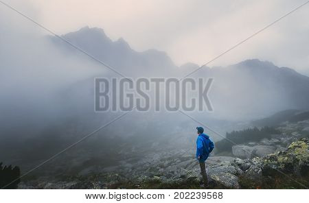 Hiker traveler in foggy mountains. Spring autumn season traveling