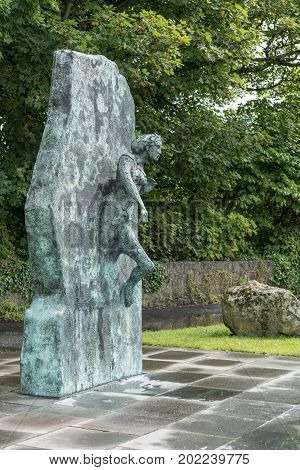 Galway Ireland - August 5 2017: Equality Emerging Statue by John Began with green trees background shows a partially covered woman stepping out of a wall. Metal turned partially green.