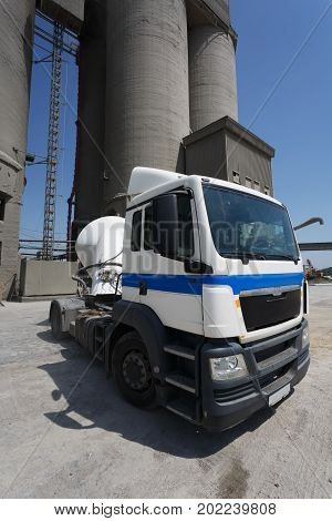 A close-up picture of a big blue and white truck on a factory background. Beautiful classic big rig semi truck with a refrigerated trailer on a road. A big car without lorry trailer. Copy space.