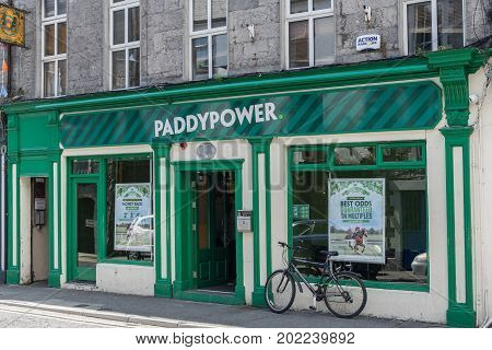 Galway Ireland - August 5 2017: The green facade of Paddypower betting company store shows street scene with bicycle open door and two display windows.