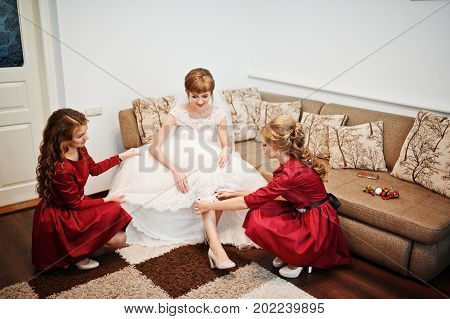 Bridesmaids Helping Bride To Put A Garter On For The Wedding.