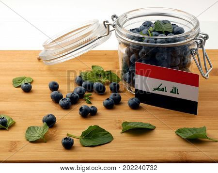 Iraqi Flag On A Wooden Plank With Blueberries Isolated On White