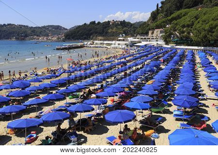 LERICI ITALY La Spezia province Ligurian Riviera - August 07 2017. Anomalous hot summer of 2017. Many tourists relax on the famous Venere Azzurra Beach. Sandy beach with blue umbrellas. Concept of beach vacation. Tourist destination
