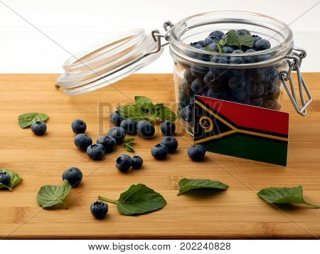 Vanuatu Flag On A Wooden Plank With Blueberries Isolated On White