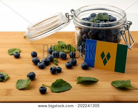 Saint Vincent And The Grenadines Flag On A Wooden Plank With Blueberries Isolated On White