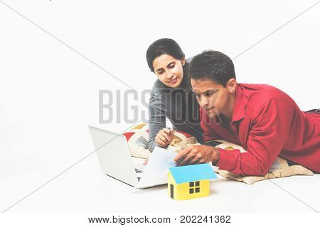 stock photo of Indian young couple doing paperwork or a loan case for new home while sitting over white background with pillow, laptop and 3d house model, Indian real estate concept