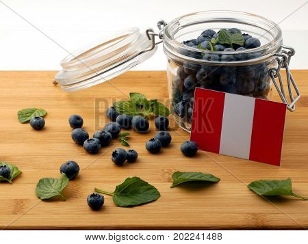 Peruvian Flag On A Wooden Plank With Blueberries Isolated On White