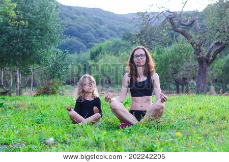 Mom And Daughter Are Sitting In A Lotus Position In Nature.