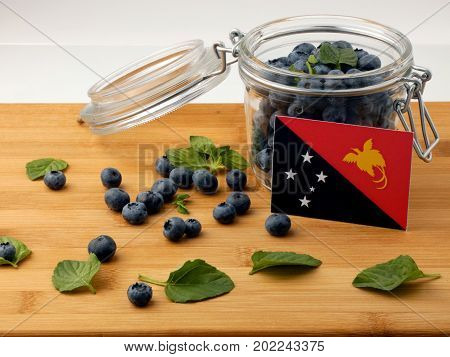 Papua New Guinea Flag On A Wooden Plank With Blueberries Isolated On White