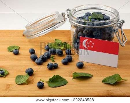 Singaporean Flag On A Wooden Plank With Blueberries Isolated On White