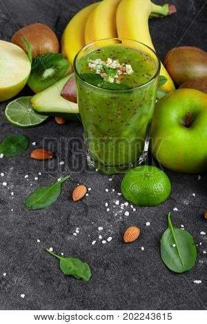 A top view of a composition of kiwi smoothie with grated nuts on a top and ripe fruits on a dark stones background. Whole and cut apples, lime, kiwi, avocado and a branch of ripe bananas on a table.