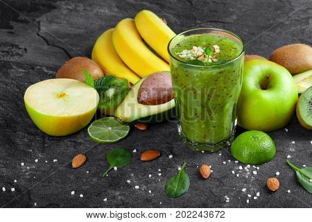 A colorful composition of kiwi smoothie with grated nuts on a top and ripe fruits on a dark stones background. Whole and cut apples, lime, kiwi, avocado and a branch of ripe bananas on a table.
