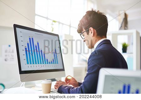 Concentrated young white collar worker in eyeglasses sitting in front of modern computer and making financial report, interior of spacious office with panoramic windows on background, profile view