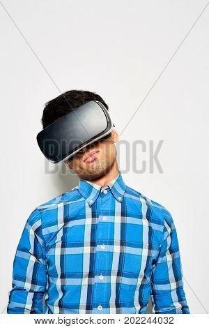 Waist-up portrait of dark-haired young designer wearing VR goggles while working on promising project, studio shot