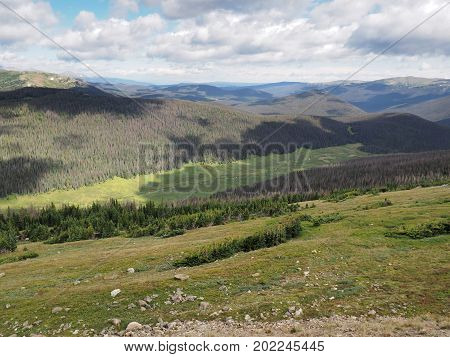 Summer in Rocky Mountain National Park in Colorado. White puffy clouds cast shadows on the mountains and meadows below.