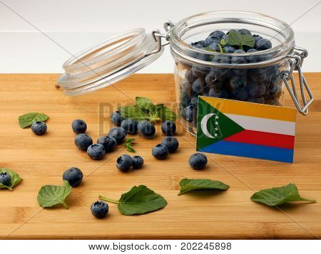Comoros Flag On A Wooden Plank With Blueberries Isolated On White