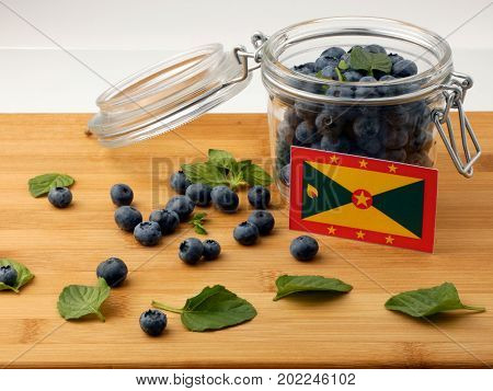 Grenada Flag On A Wooden Plank With Blueberries Isolated On White