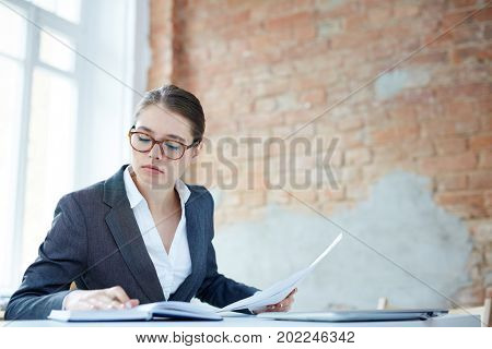 Young auditor reading her notes in notebook while working with papers