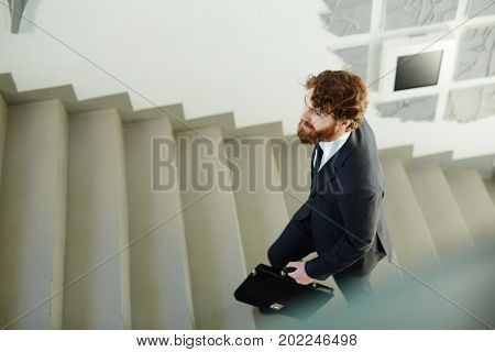 Businessman with briefcase going upstairs on staircase