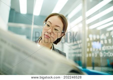 Serious businesswoman with newspaper reading financial news