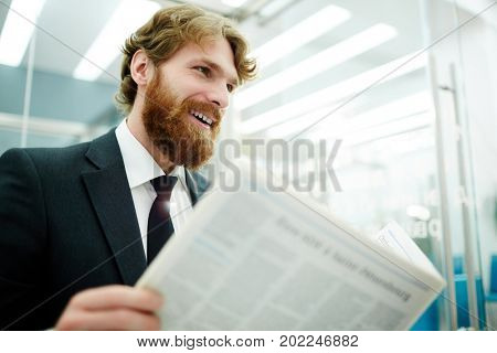 Bearded man with newspaper searching for vacancy on job adverts page