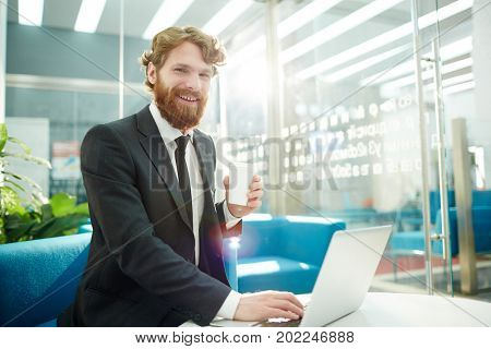 Successful employer with drink looking through online resumes of applicants in office