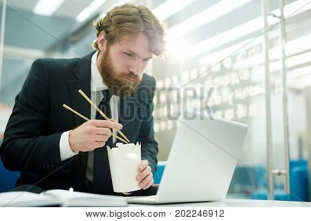 Hungry businessman eating chinese noodles from box in front of laptop at lunch break in office