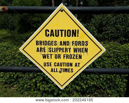 a yellow diamond shaped caution slippery when wet sign