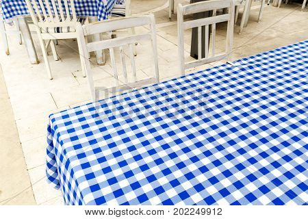 Empty Table Covered With Blue And White Chequered Tablecloth Next To White Wooden Chairs.