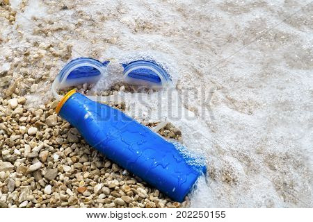 Swimming Goggles And Suntan Lotion Lying On Pebble Beach In Water.