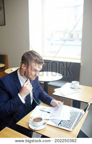 Young employer or agent with earphones speaking through video-chat